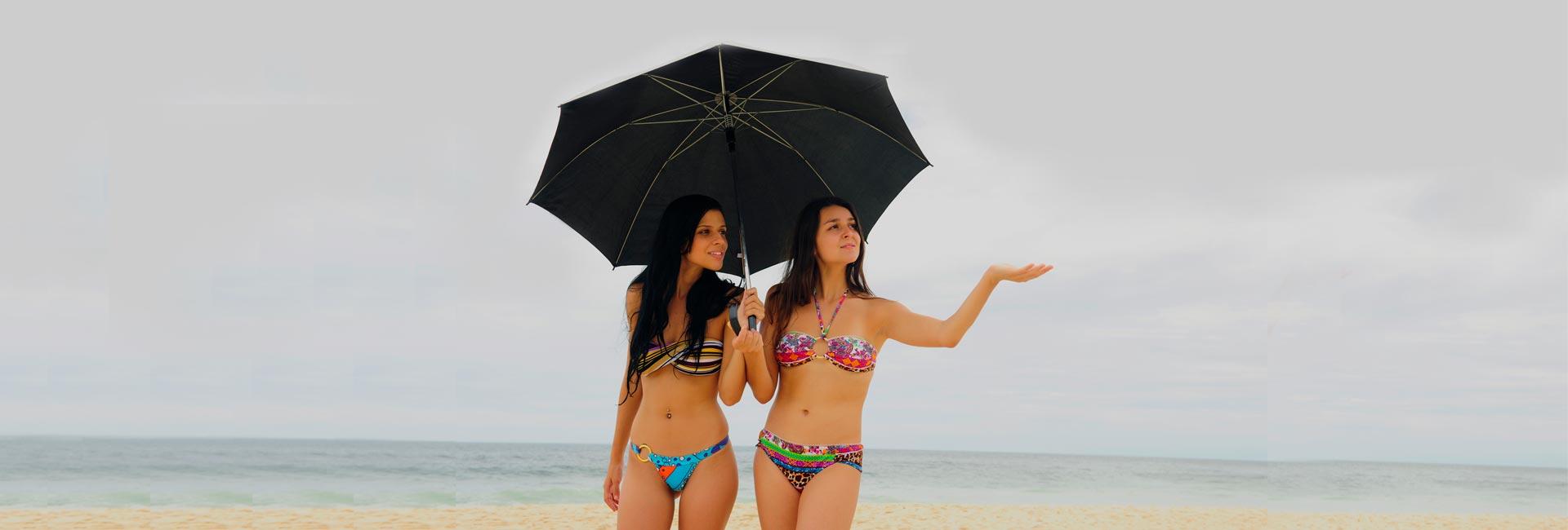 Optimizada two women with umbrella at puerto vallarta beach